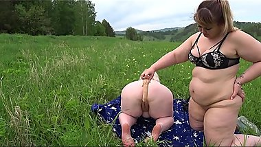 Lesbians BBW having fun outdoors on the grass. Mature milf doggystyle in mini bikini shakes big tits and fat butt.